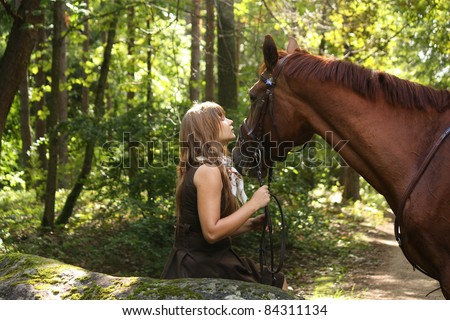 Beautiful young girl in brown dress and chestnut horse at the forest