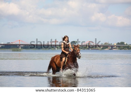 Beautiful young girl in brown dress and chestnut horse riding in the water