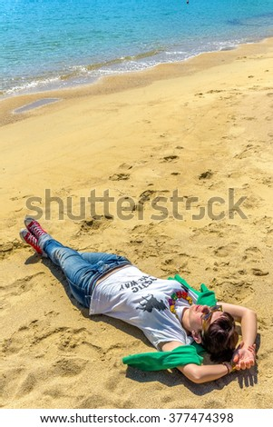 Beautiful young girl in casual outfit lying on a magnificent beach in Mykonos, Greece. - stock photo