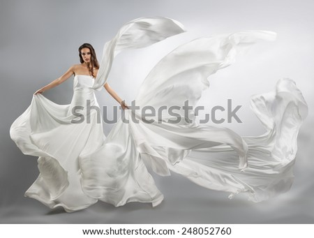 beautiful young girl in flying white dress. Flowing fabric - stock photo