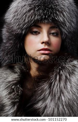 Beautiful young girl in fur clothes. Studio shot - stock photo