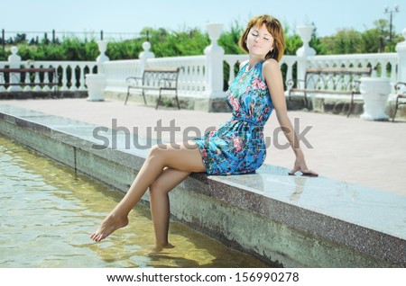 Beautiful young girl in green summer park. happy redhead woman posing outdoors, sitting near the fountain. Romantic lady at vacation holidays, putting her legs in the water and sunbathing