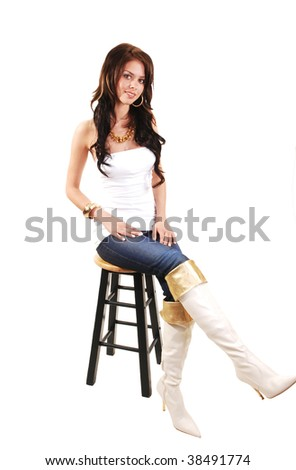 Beautiful young girl in jeans and long white boots and jeans sitting on  a bar chair in the studio and smiling.