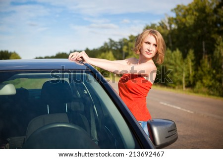 Beautiful young girl in red clothes near the car on nature