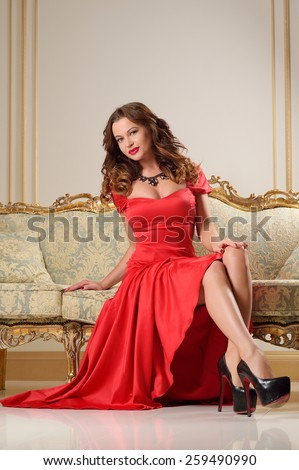 Beautiful young girl in red dress with big breasts, full lips, slim, athletic build, brunette with red lipstick in the interior of the Renaissance in beige and golden tones - stock photo
