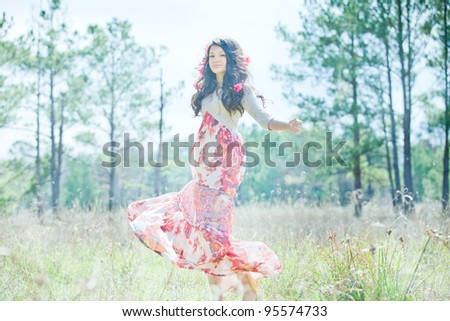 Beautiful Young Girl in Red Flower Dress Smilingly Whirling in Grassy Meadow