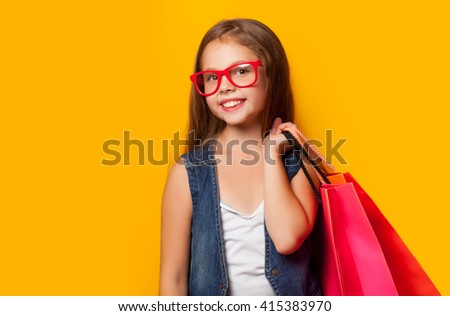 Beautiful young girl in red glasses with shopping bags on yellow background. - stock photo