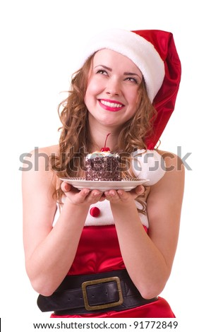 Beautiful young girl in Santa Claus clothes with tasty cake on white background.