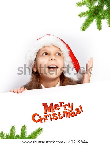 Beautiful young girl in santa hat behind white board. Space for text isolated on white.  - stock photo