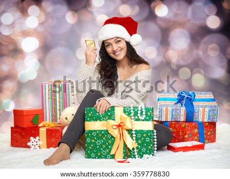beautiful young girl in santa hat with a glass of champagne and gift boxes - stock photo
