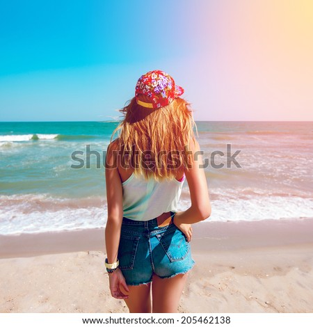 Beautiful young girl in stylish colored  swag hat and  jeans shorts  posing  on a tropical beach.Warm, sunny colors and mood - stock photo