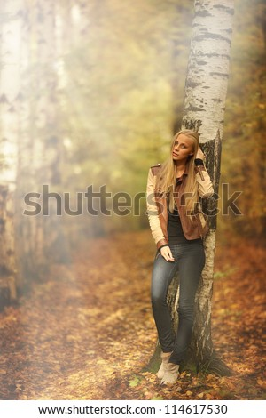 beautiful young girl in the autumn forest - stock photo