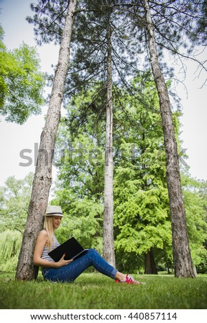 Beautiful young girl in the park leaning on a tree and read a book. Relaxation. - stock photo