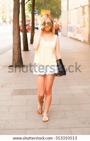 beautiful young girl in the street with the phone