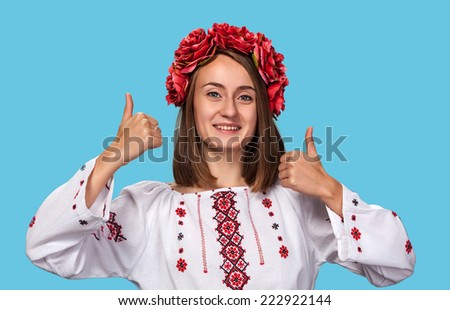 Beautiful young girl in the Ukrainian national suit isolated on blue  - stock photo