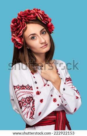 Beautiful young girl in the Ukrainian national suit isolated on blue