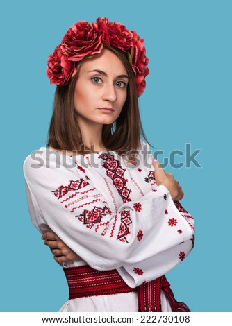 Beautiful young girl in the Ukrainian national suit isolated on blue background - stock photo