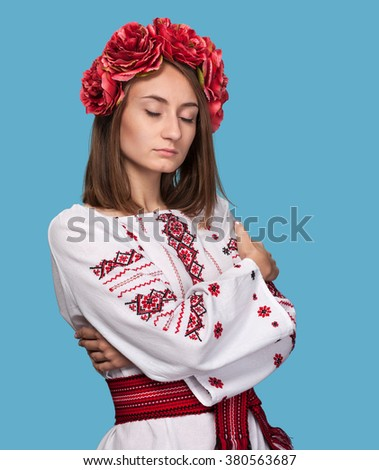 Beautiful young girl in the Ukrainian national suit with closed eyes isolated on blue