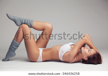 beautiful young girl in white lingerie and long grey socks lying on a light background