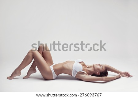 beautiful young girl in white lingerie lying on a light background