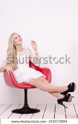 Beautiful young girl in white short dress sitting on modern red chair with legs stretched, high heels, professional make-up. happy