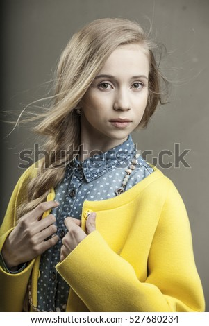 beautiful young girl in yellow coat and blue shirt