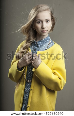 beautiful young girl in yellow coat with blonde hair and green eyes