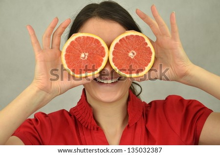 Beautiful young girl is holding a red grapefruit