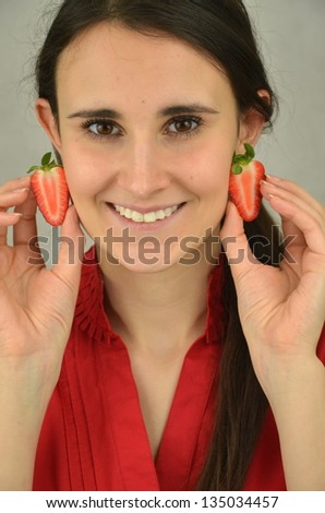 Beautiful young girl is holding strawberries