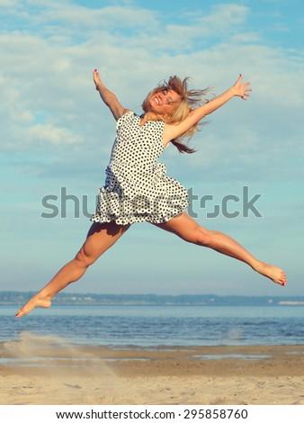 Beautiful young girl jumping on sea - stock photo