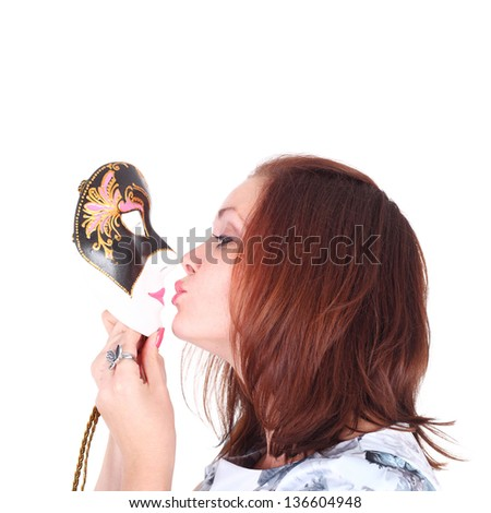 beautiful young girl kissing the theatrical mask - stock photo