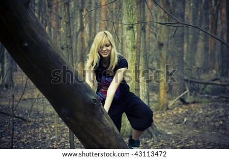 beautiful young girl leaned on a tree trunk in the forest