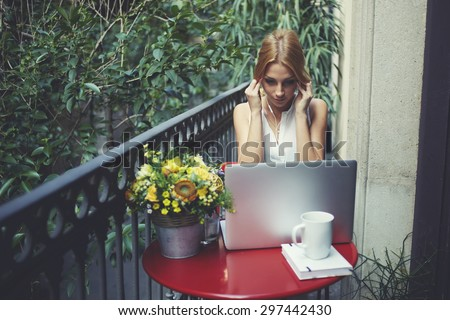 Beautiful young girl listening to music with headphones while sitting in front of an open laptop,attractive woman watching the movie on a laptop computer using headphones,home work area with computer - stock photo