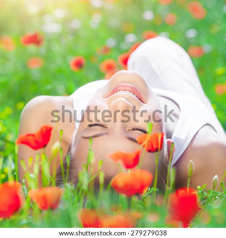 Beautiful young girl lying down on fresh poppy flower field, closing eyes of pleasure, enjoying amazing spring time sunny day - stock photo