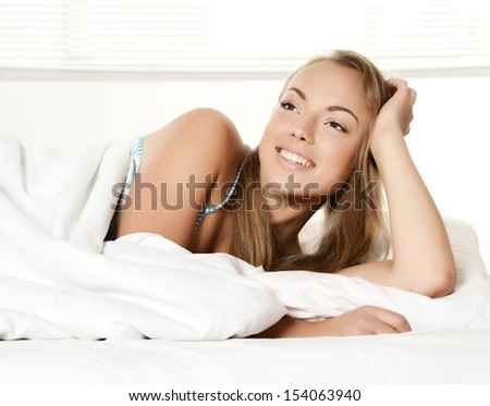 Beautiful young girl lying in white bed