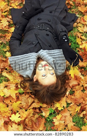 Beautiful young girl lying on fall leaves outdoors