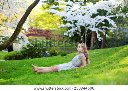 Beautiful young girl lying on the grass in cherry blossom garden on a spring day - stock photo