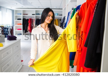 beautiful young girl measures the dress in the shop.girl on a shopping - stock photo