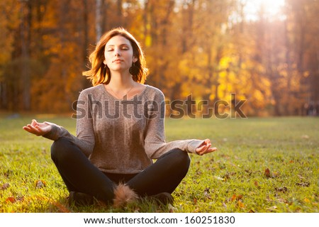 Beautiful young girl meditating in autumn park - stock photo