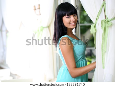 Beautiful young girl near window in room - stock photo