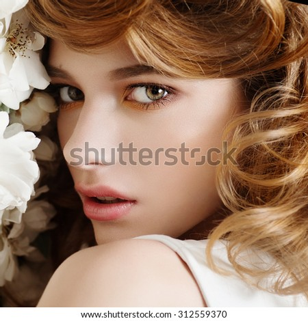 Beautiful young girl on a background of white flowers, the concept of beauty  - stock photo