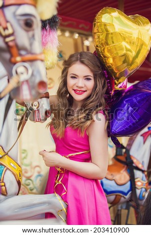 Beautiful young girl on a merry go round