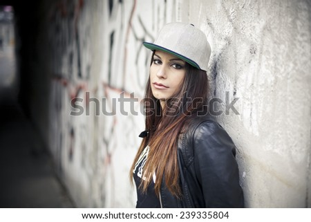 Beautiful young girl on a wall background - stock photo