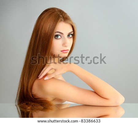 Beautiful young girl on gray background
