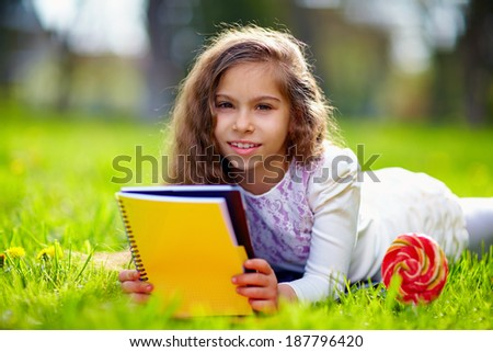 beautiful young girl on green meadow with notebook