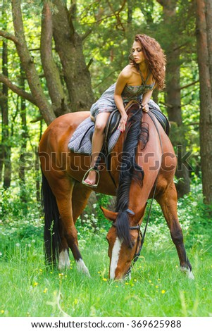 beautiful young girl on horse in dress in forest