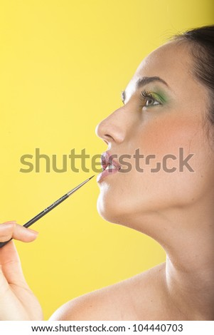 Beautiful young girl on the full beauty treatment. Make-up and hairdressing. Isolated on yellow background