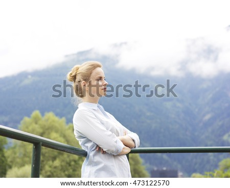Beautiful young girl on the nature in the highlands. Young girl outdoors alone. Dreamy girl sitting near the country house