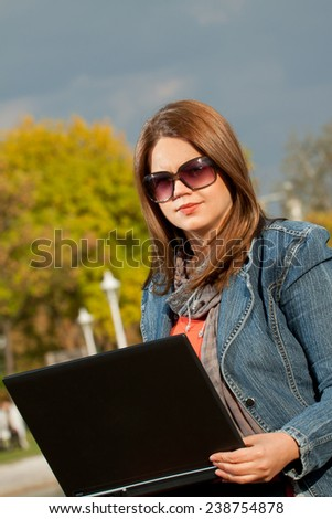 Beautiful young girl outdoor with laptop - stock photo