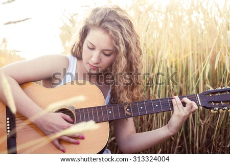 Beautiful young girl playing guitar in the golden wheat field. Lens flare, selective focus, toned image. - stock photo